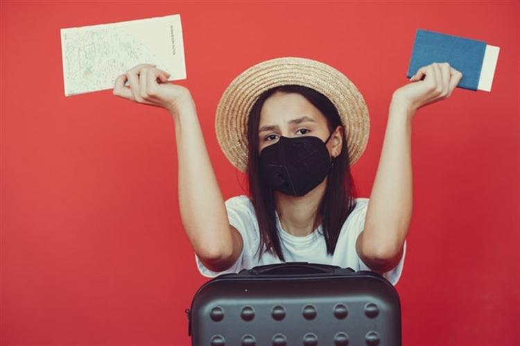 reizende passagier met mondkapjeen paspoort